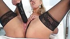 Busty blonde playing with pussy lips and huge dildo